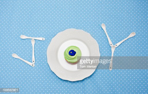 Teaspoons and plate with cupcake spelling 'joy' on tablecloth : Stock Photo