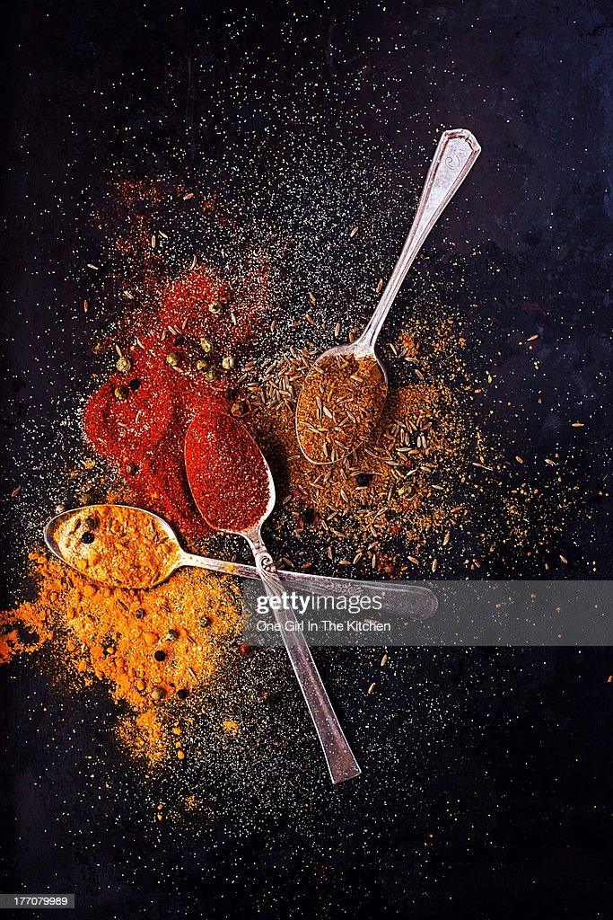 Teaspoons with ground spices on dark background