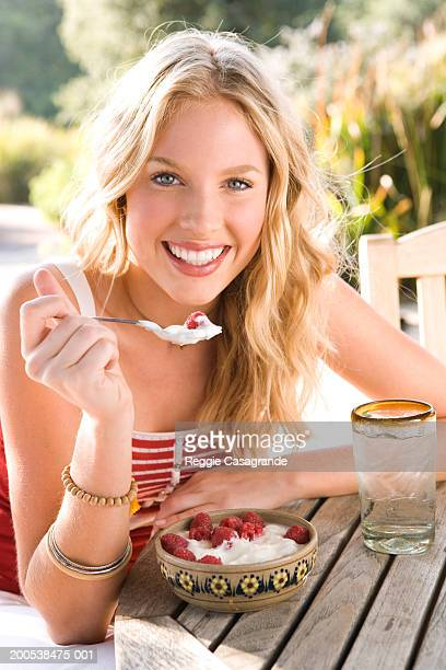 Tecate, Mexico, young woman smiling, eating yogurt, berries, portrait