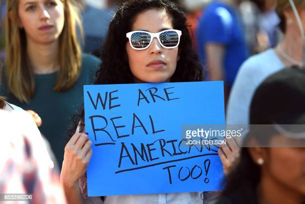 Tech employee Natalie Rios holds a sign during Tech Stands Up rally against President Donald Trump in Palo Alto California on March 14 2017 / AFP...