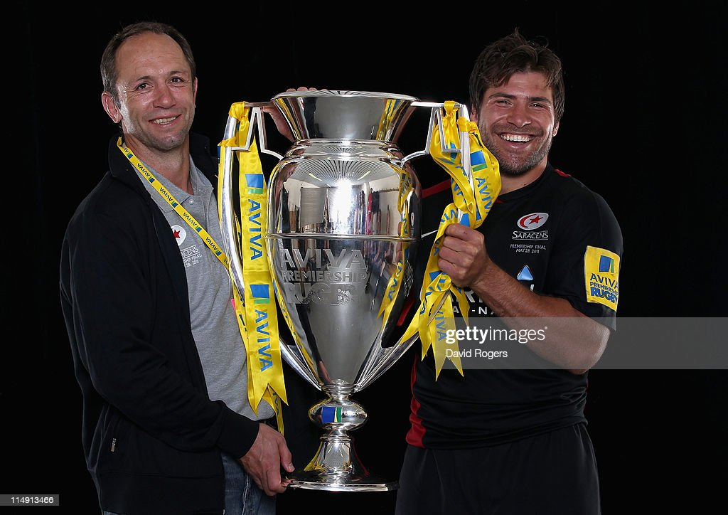 Technical Director of Saracens Brendan Ventor and 'Man of the Match' Schalk Brits of Saracens pose with the trophy following victory in the AVIVA...