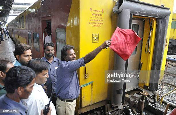Technical staff show a red flag while connecting the locomotive with Indore bound Double Decker AC Express at Bhopal station on last day of its run...