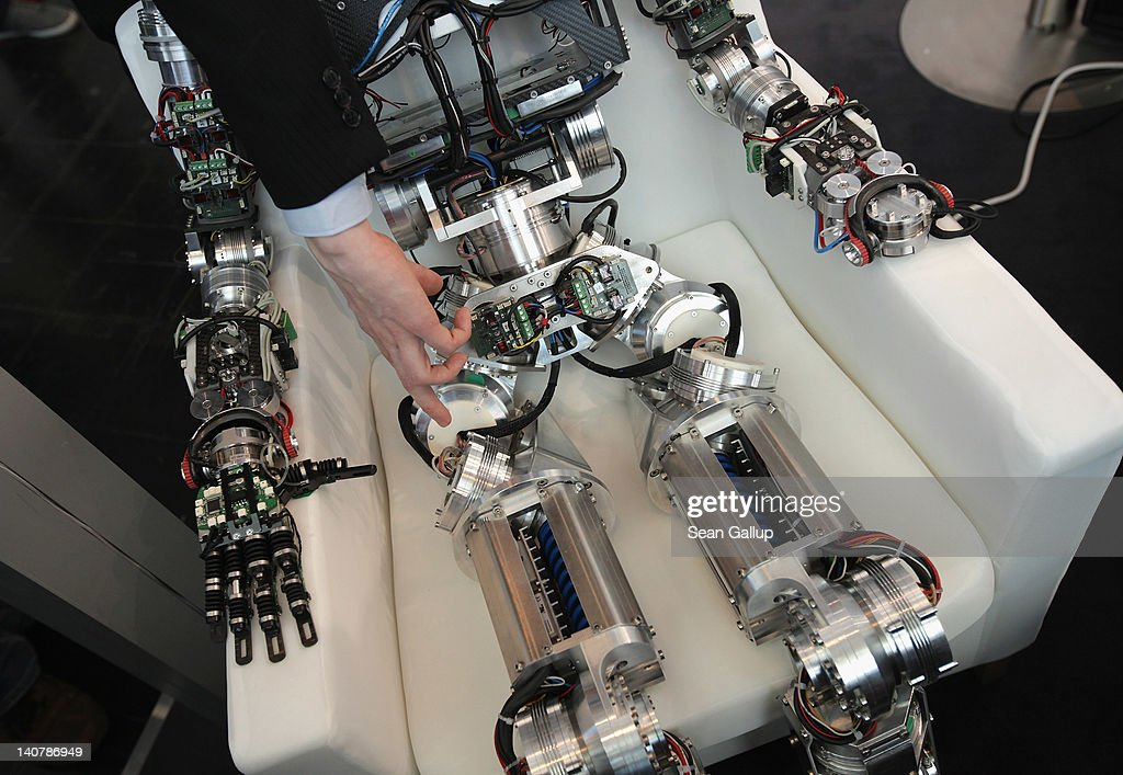A technican points to th hip of a robot developed by the Karlsruhe Institute of Technology and sitting in a chair on the first day of the CeBIT 2012 technology trade fair on March 6, 2012 in Hanover, Germany. CeBIT 2012, the world's largest information technology trade fair, will run from March 6-10, and advances in cloud computing and security are major features this year.