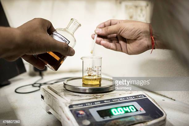 A technician adds methyl anthranilate to oils in the aroma oil laboratory at the Fragrance Flavour Development Centre in Kannauj Uttar Pradesh India...