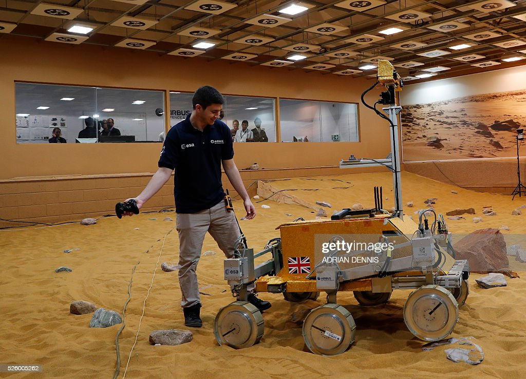 A technician adjusts a prototype Mars rover in a simulated Mars environment at the Airbus Defence and Space company in Stevenage on April 29, 2016. British astronaut Major Tim Peake will remotely navigate the rover through the Martian landscape from the International Space Station, part of a project to learn how astronauts can control remote systems. / AFP / ADRIAN