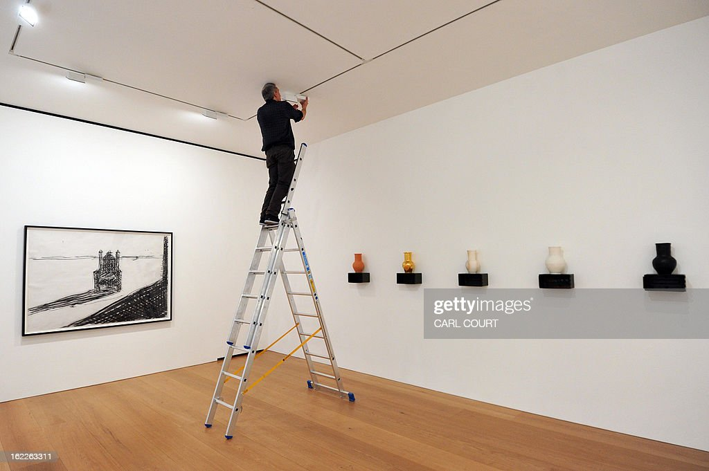 A technician adjusts lights next to works by French artist Adel Abdessemed entitled 'The Twang of the Void' (L) and 'Le Vase abominable 2: little pot, salt pot, ordinary pot, gum pot, ukrainian pot' at the David Zwirner Gallery in central London on February 21, 2013 The pieces make up part of Adel Abdessemed's new show, 'Le Vase abominable,' and runs at the gallery until March 30, 2013.