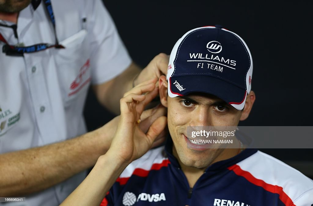 A technician (L) adjusts the microphone of William's Venezuelan driver Pastor Maldonado during a press conference on April 18, 2013 at the Bahrain International Circuit in Manama ahead of the Bahrain Formula One Grand Prix.