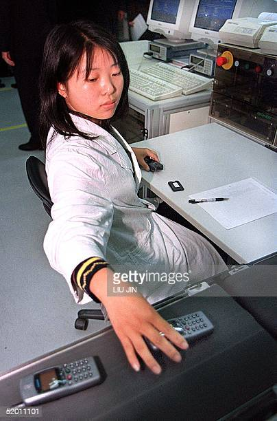 A technician assembles and tests mobile phones 04 November 1999 at an overseas firm's factory in Shanghai China is rolling out aggressive policies to...