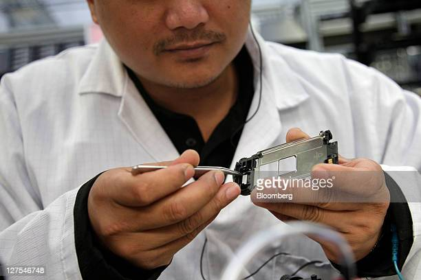 A technician assembles components during the initial assembly of a mobile handset at Nokia Oyj's Vertu luxury phone division in Church Crookham UK on...