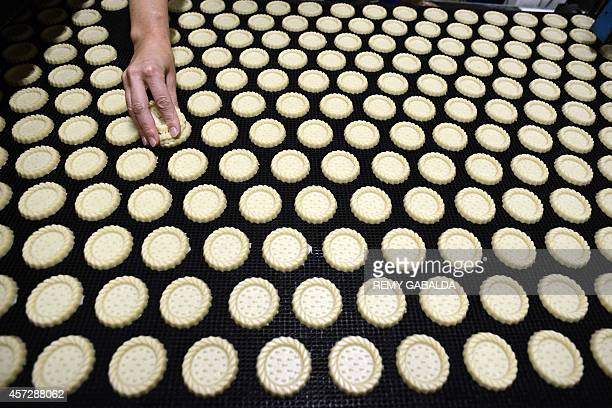 A technician at the French firm Poult specialized in the manufacture of cookies for supermarkets checks on October 15 2014 the quality of products on...