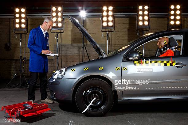 A technician checking a crash test car