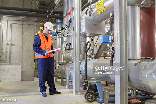 Technician checking paperwork in power station