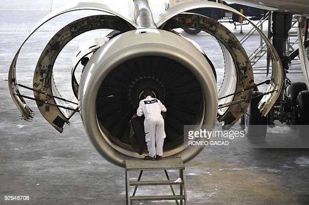 A technician checks the Rolls Royce engine of Garuda Indonesia's Airbus A330300 aircraft at the company hangar in Jakarta airport on July 15 2009...
