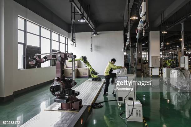 A technician climbs a set of step ladders next to industrial robots on the testing line of a factory operated by EDeodar Robot Equipment Co a...