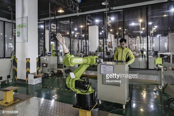 A technician controls an industrial robot fitted with an artifical hand on the testing line of a factory operated by EDeodar Robot Equipment Co a...
