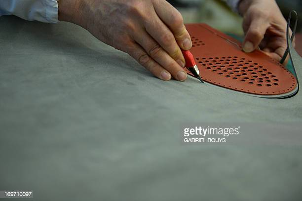 A technician cuts the shape of a peeble sole in a grey skin in the protopypes' workshop of the Italian shoes and luxury leather goods Tod's on May 27...