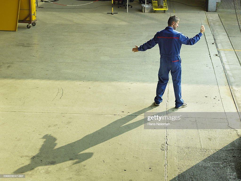 Technician directing aircraft into hangar