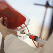 Technician drawing blood with syringe from blood bag, Close-up of hands