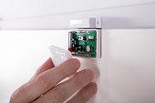 Close-up Of A Technician's Hand Fixing Security System Door Sensor