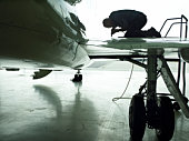 Technician fixing wing of private plane in hangar, silhouette