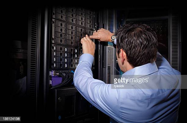 IT Technician From Behind Repairing Server in Network Bay