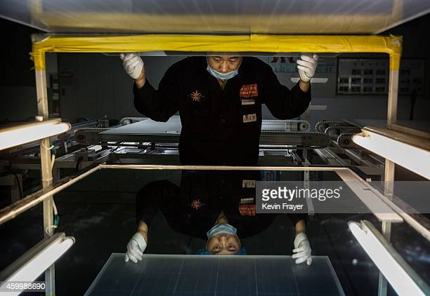 Technician from Yingli Solar checks a solar panel in the final stage of production at the company's headquarters on December 4 2014 in Baoding Hebei...