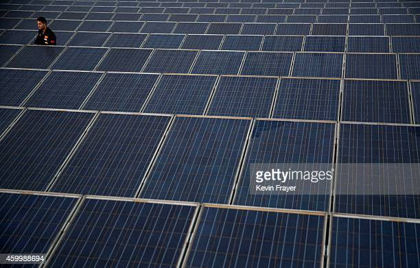A technician from Yingli Solar checks a solar panel used to produce energy for lighting on the roof at the company's headquarters on December 4 2014...