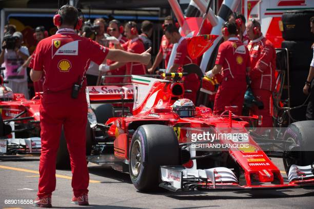 A technician gestures to Ferrari's Finnish driver Kimi Raikkonen in the pit during the third practice session at the Monaco street circuit on May 27...