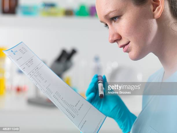 Technician holding blood sample in clinical laboratory with test results