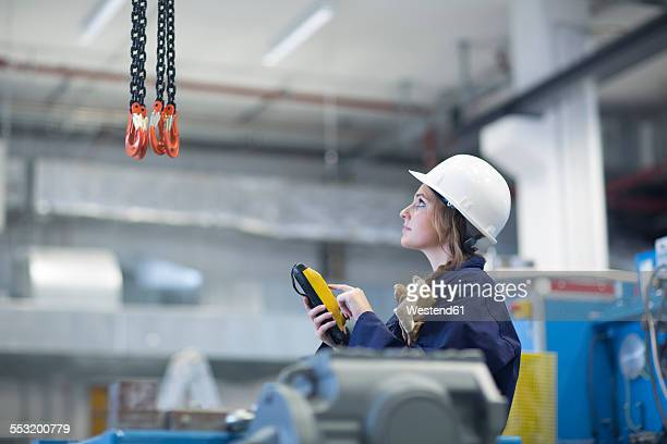 Technician in factory hall using regulator for hook