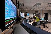 Technician in hard hat monitoring computer screens in control room