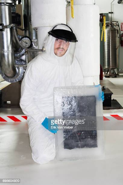 technician in protective clothing displays laptop frozen in solid ice