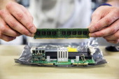 A technician inserts a random access memory board into a slot on a motherboard during the assembly of computer server units at the Bull SA...