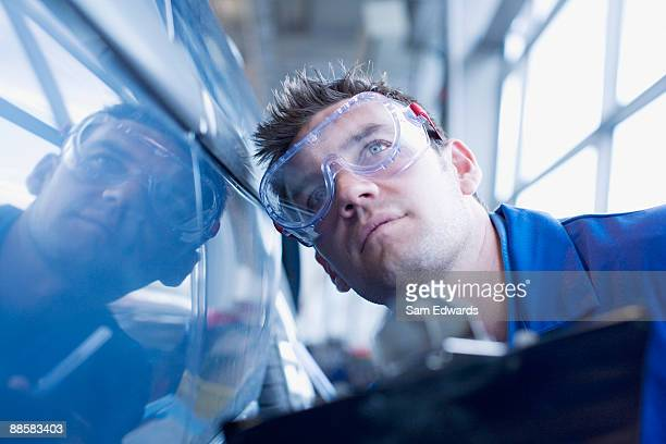 Technician inspecting car