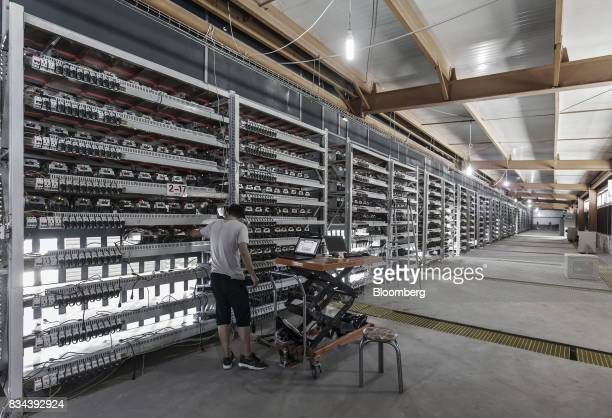 A technician inspects bitcoin mining machines at a mining facility operated by Bitmain Technologies Ltd in Ordos Inner Mongolia China on Friday Aug...