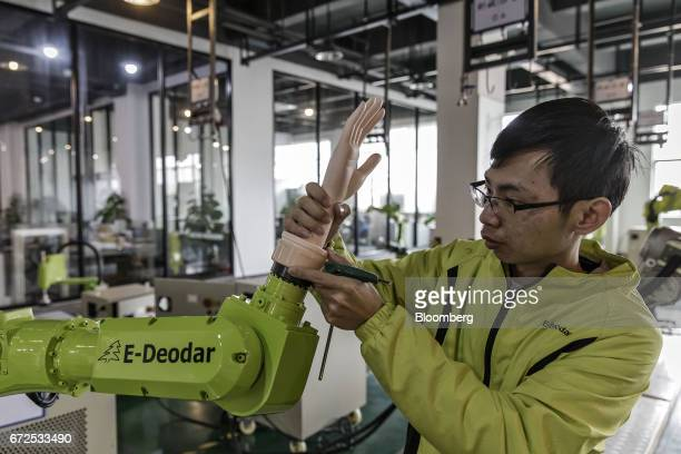A technician installs an artificial hand onto an industrial robot at a factory operated by EDeodar Robot Equipment Co a whollyowned subsidiary of...
