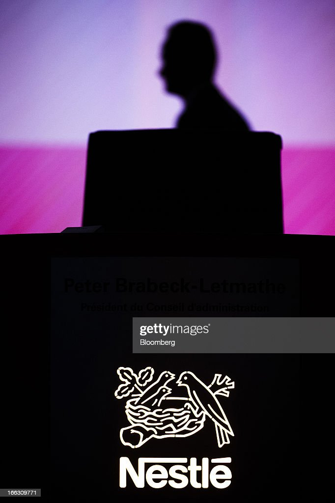 A technician is silhouetted behind an illuminated Nestle SA logo ahead of the company's annual general meeting (AGM) in Lausanne, Switzerland, on Thursday, April 11, 2012. Nestle SA's chairman said Switzerland is becoming more difficult as a business location after voters last month approved some of the world's toughest limits on executives' pay. Photographer: Valentin Flauraud/Bloomberg via Getty Images