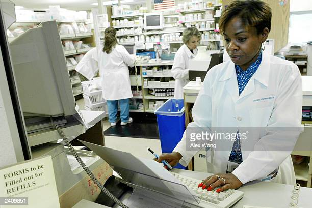Technician Joan Garner helps to process prescription requests August 19 2003 at a pharmacy of the Woodbridge Medical Center in Woodbridge Virginia...