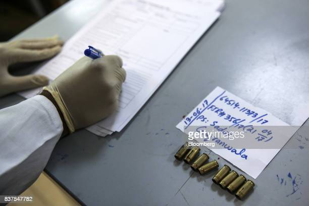 A technician makes notes on bullet casings in a laboratory at the Firearms and Tool Marks Identification Department of th Punjab Forensic Science...