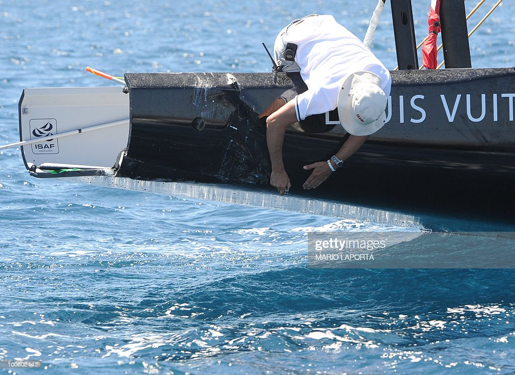 A technician of the Louis Vuitton Cup organization looks at the damage to a boat helmed by Italian team Azzura following a collision with a boat crewed by the French Aleph team at the start of a Louis Vuitton Cup regatta on May 25, 2010 at La Maddalena island in Sardinia. Ten teams are battling it out over a two-week regatta until June 6.