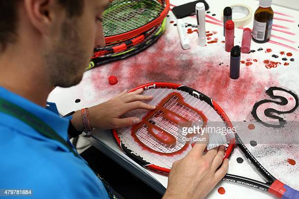 A technician paints a logo onto the strings of a restrung racquet in the restringing workshop on day 8 of the Wimbledon Lawn Tennis Championships at...