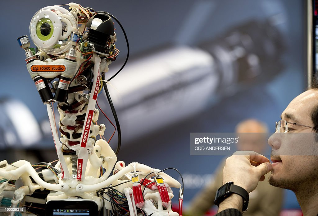 A technician performs electronic surgery by replacing a thin cable on a robot at Maxon Motors' booth at the industrial trade fair in Hanover, central Germany on April 8, 2013. The fair running from April 8 to 12, 2013 presents a cross section of key industrial technologies. AFP PHOTO / ODD ANDERSEN