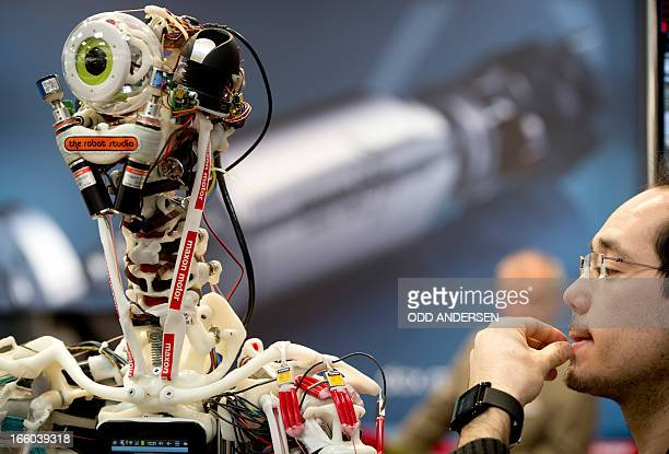 A technician performs electronic surgery by replacing a thin cable on a robot at Maxon Motors' booth at the industrial trade fair in Hanover central...
