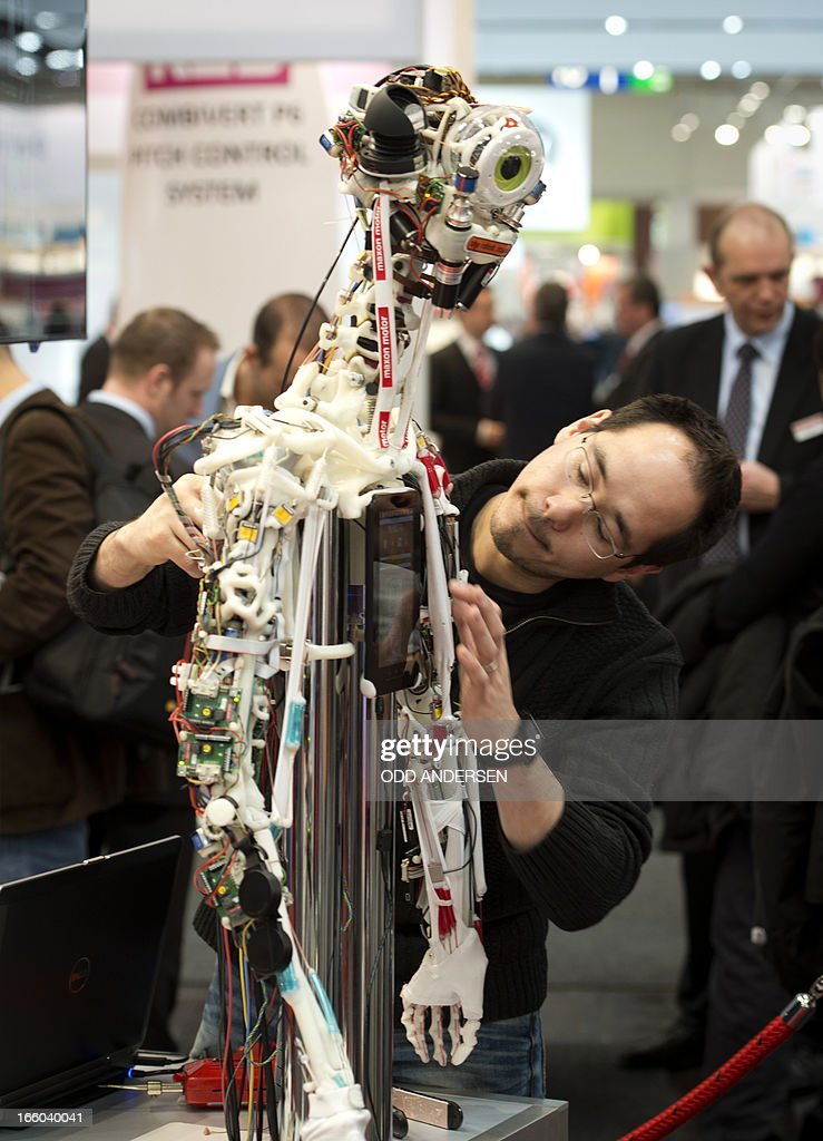 A technician performs electronic surgery by replacing a thin cable on a robot at Maxon Motors' booth at the industrial trade fair in Hanover, central Germany on April 8, 2013. The fair running from April 8 to 12, 2013 presents a cross section of key industrial technologies.