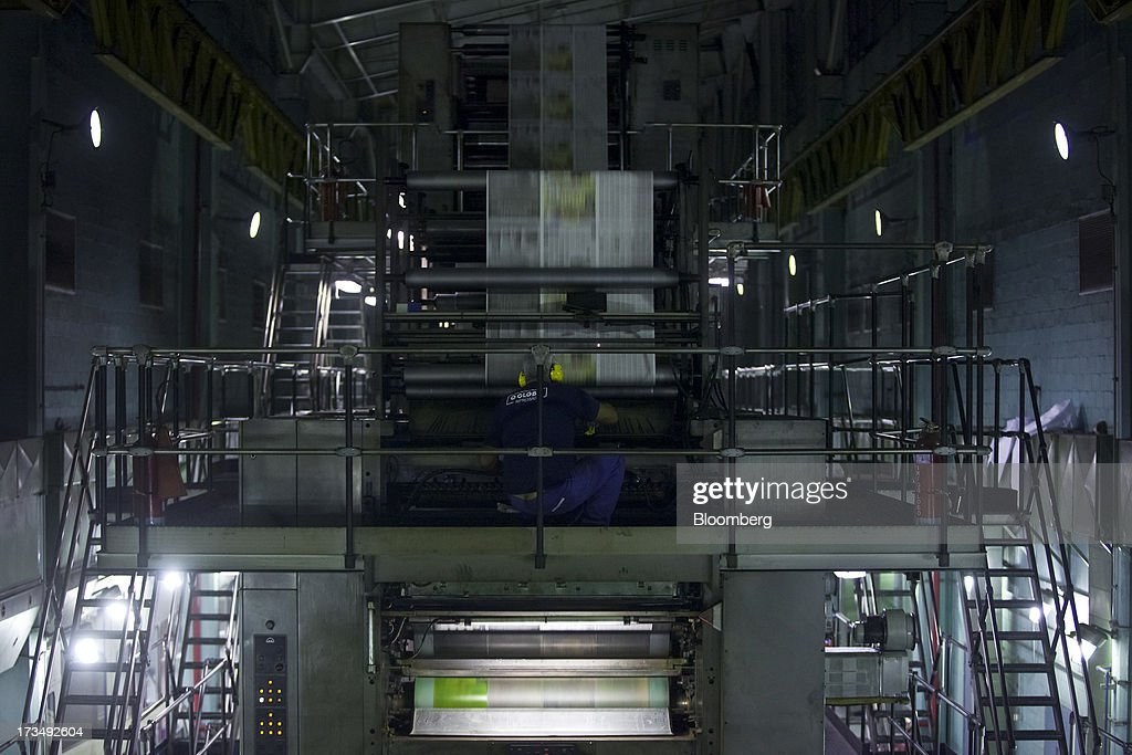 A technician performs maintenance to a press during the printing of the O Globo newspaper in Rio de Janeiro, Brazil, on Friday, July 12, 2013. Brazil economists raised their 2014 benchmark interest rate forecast to the highest all year, as policy makers work to slow inflation that has curbed consumption and confidence in the world's second-biggest emerging market. Photographer: Dado Galdieri/Bloomberg via Getty Images