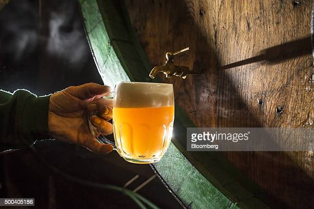 A technician pours a draft of beer from a storage vat to inspect the quality at the Pilsner Urquell brewery operated by SABMiller Plc in Plzen Czech...