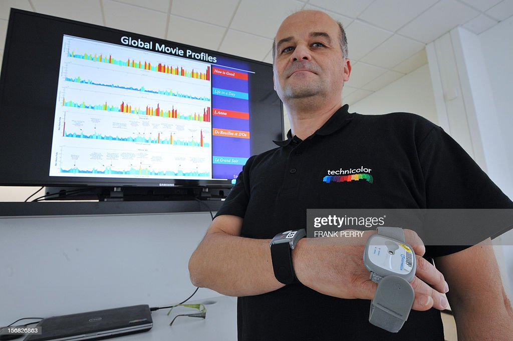 A technician presents a bracelet harnessed with physiological captors capable of registering emotions during the press conference inaugurating the new Technicolor research and development centre in Cesson-Sevigne near the central western city of Rennes on November 22, 2012. AFP PHOTO FRANK PERRY