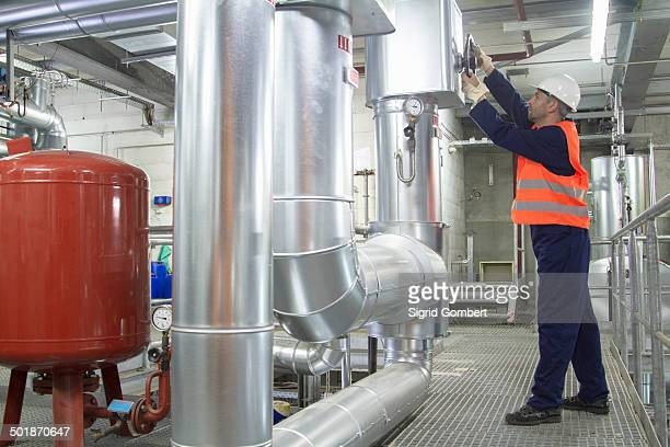 Technician reaching to check pipes in power station