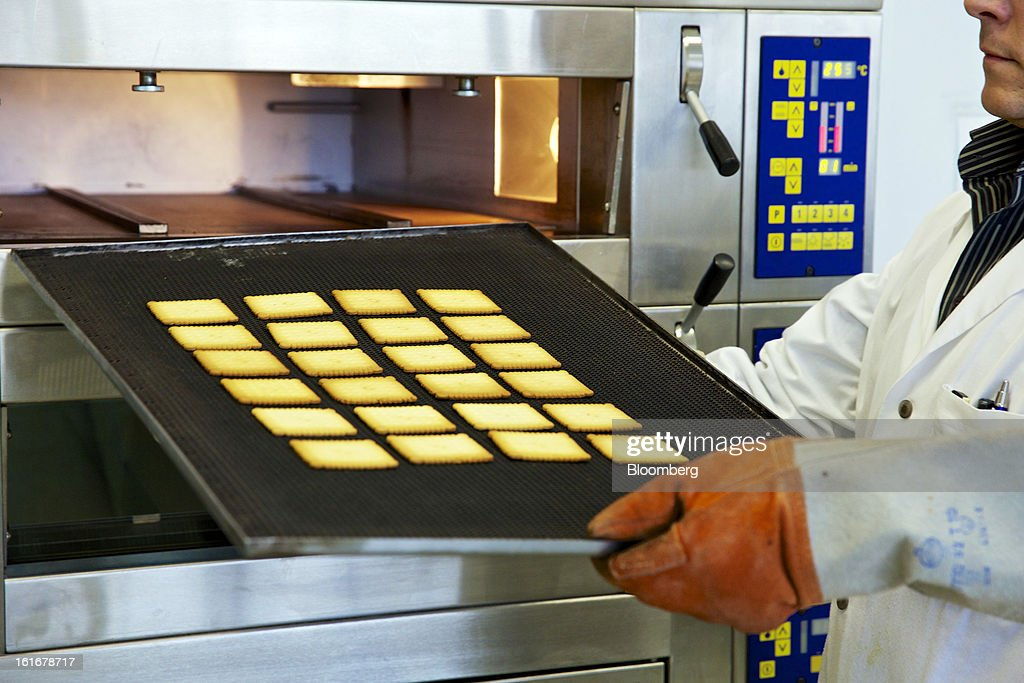 A technician removes a sample of freshly-baked butter biscuits from an oven ahead of testing at Givaudan SA's flavor research laboratory inside the company's headquarters in Dubendorf, Switzerland, on Wednesday, Feb. 13, 2013. Givaudan SA, the world's largest maker of flavorings and fragrances, announced a bigger-than-estimated dividend after riding out a year of high raw-material prices and a strong Swiss franc. Photographer: Gianluca Colla/Bloomberg via Getty Images