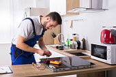 Male Technician Repairing Induction Stove With Digital Multimeter In Kitchen